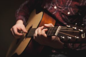 Acoustic guitar. Private artist creating art for the public. Which does the audience own?